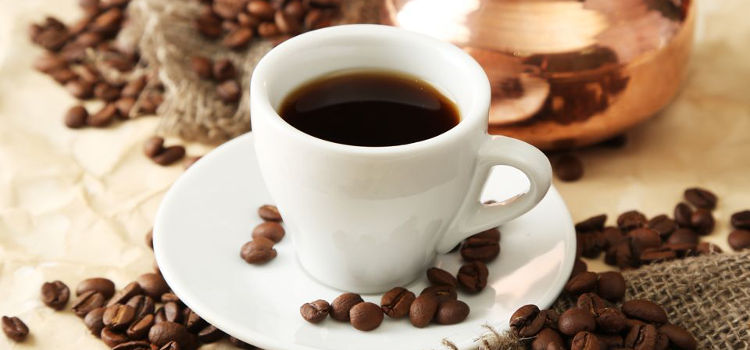 Cup and pot of coffee on beige background